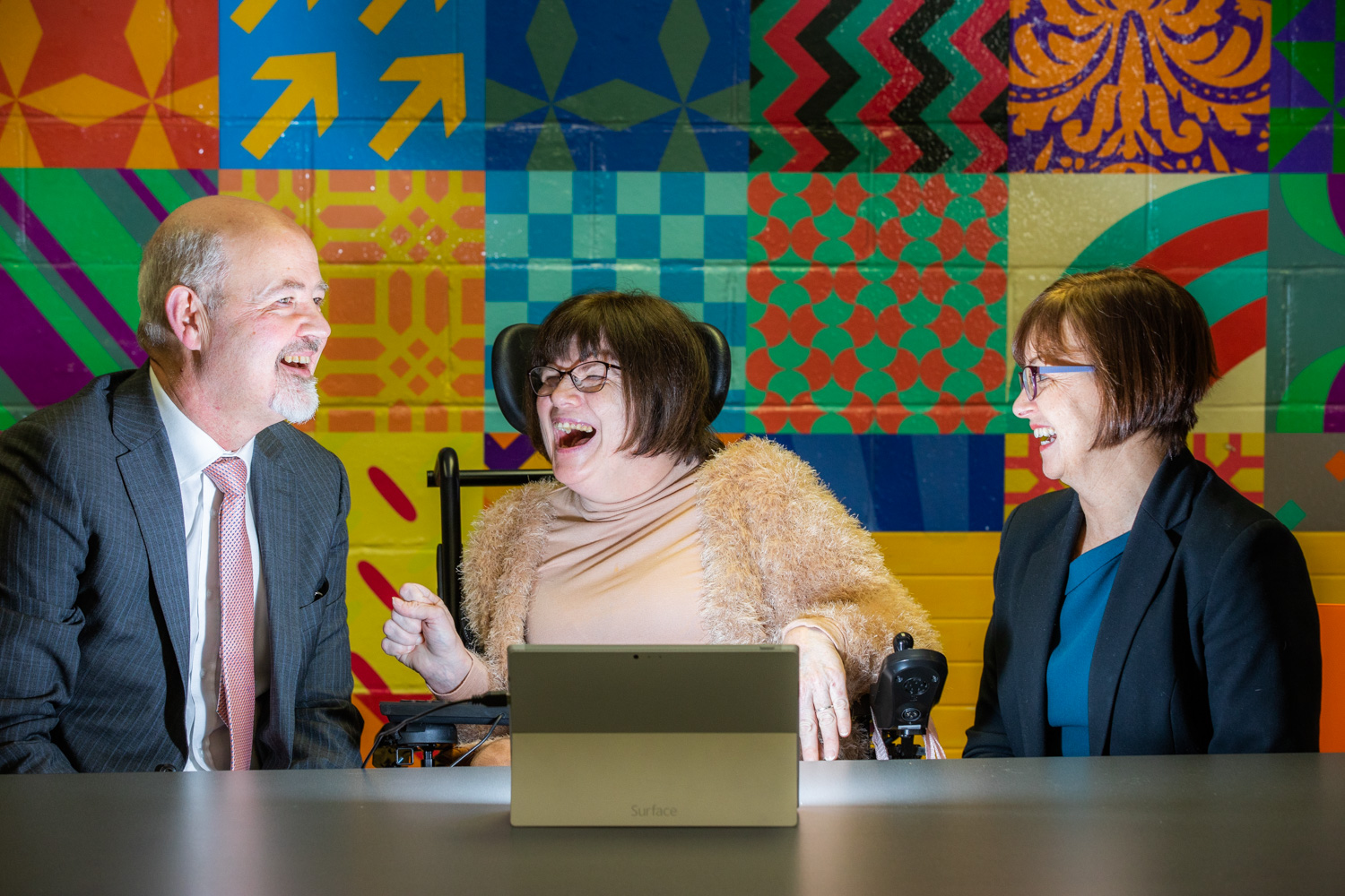 Imelda from Enable Ireland laughs with Enable Ireland CEO John O'Sullivan and Microsoft CEO Cathriona Hallahan