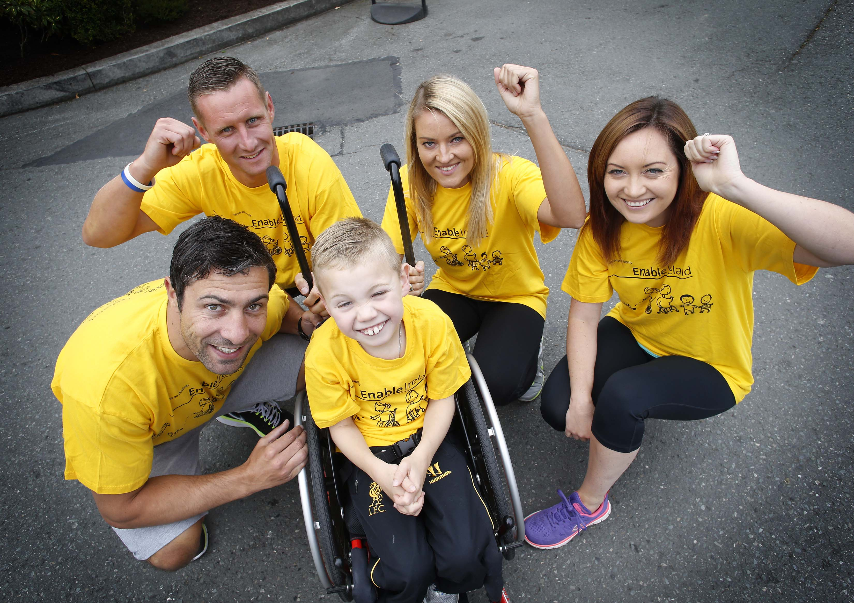 Young boy in Enable Ireland t-shirt using a wheelchair and surrounded by four adults also in yellow Enable Ireland t-shirts smiling