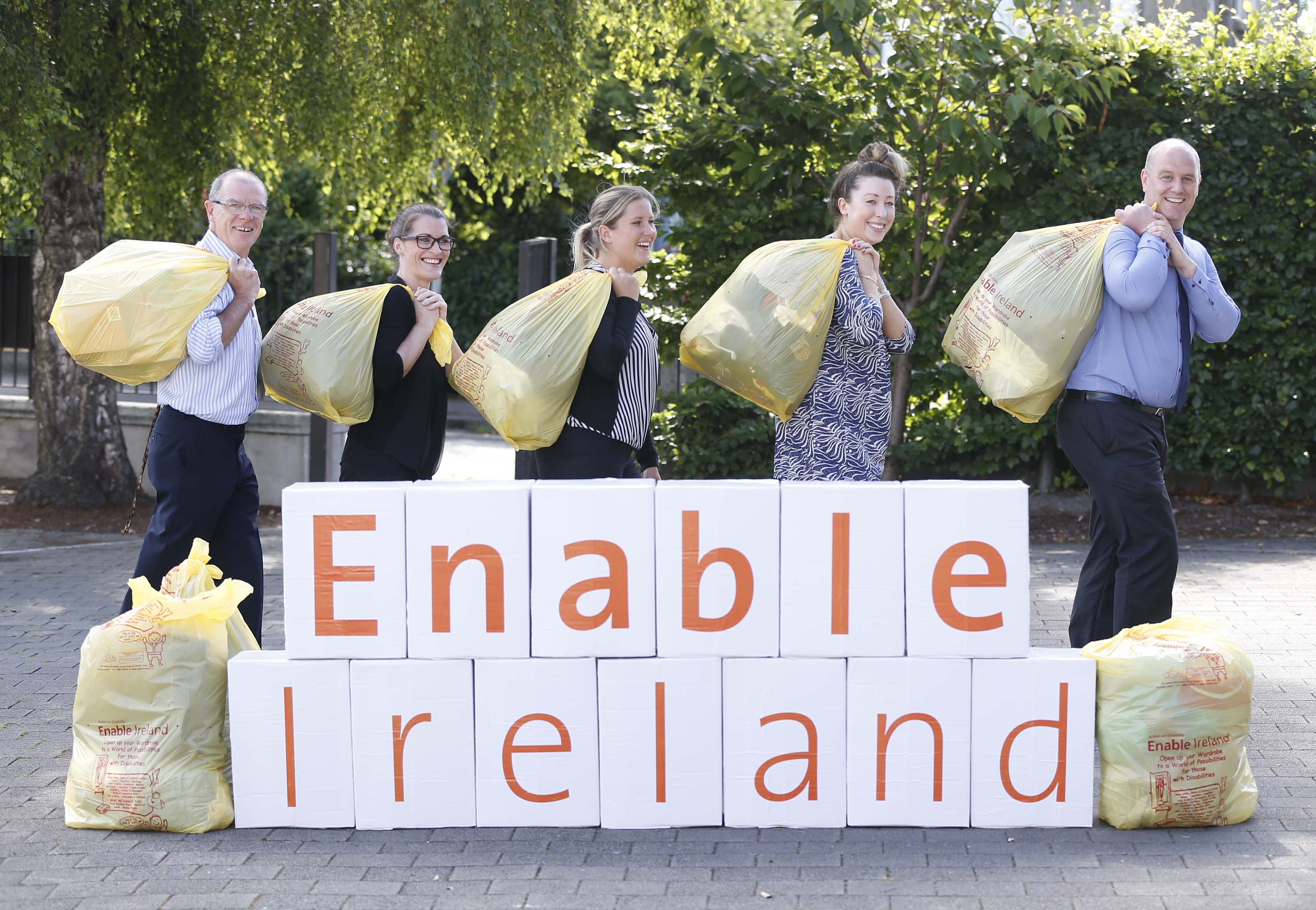 Five inidivduals in office attire standing behind and Enable Ireland sign carrying yellow Enable Ireland clothing bags over their shoulders