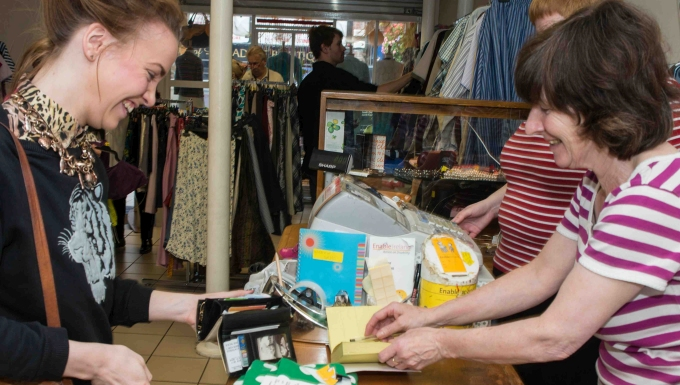 This image shows a lady purchasing a top at the till in one of our charity shops