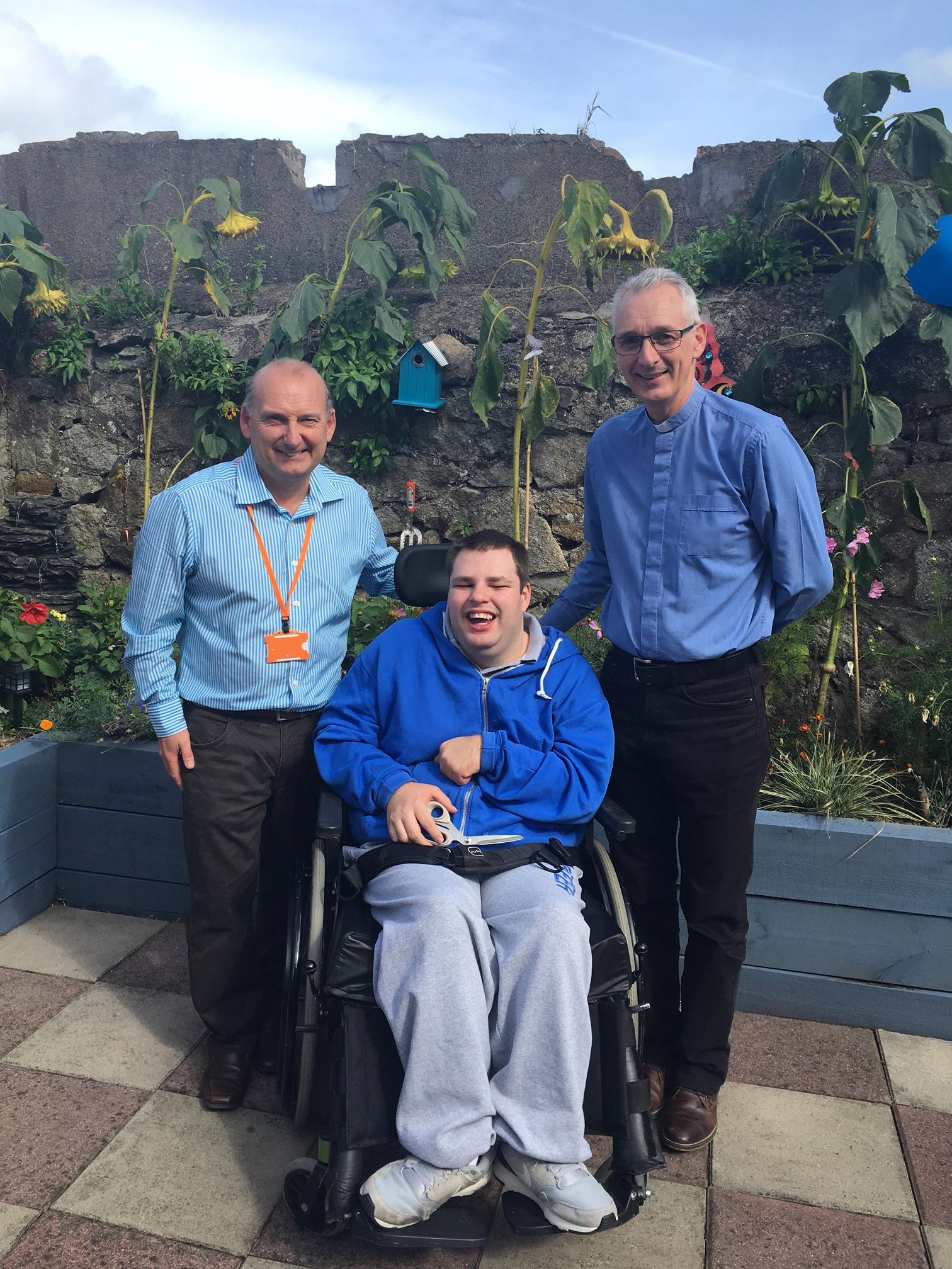 Two men and one wheelchair user in front of a sunny garden wall
