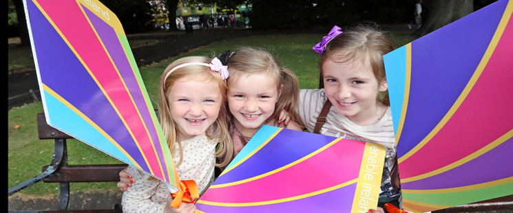 Three girls siting on a park bench holding colourful kites