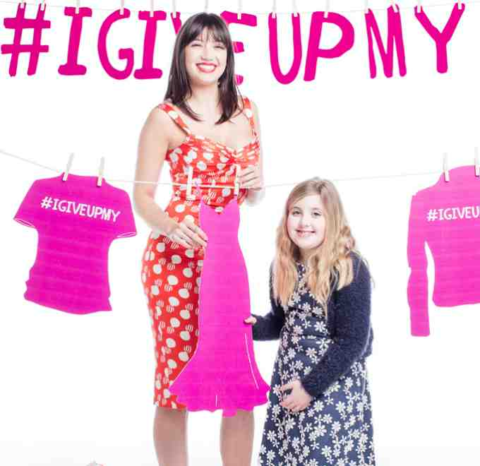 Daisy Lowe and Enable Ireland service user Ava McHugh stand beside a clothes line with slogan #IGiveUpMy in background
