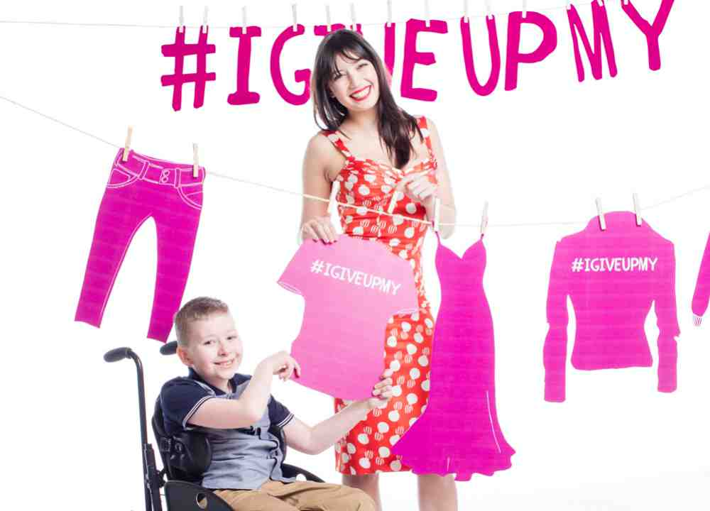 Daisy Lowe and Enable Ireland service user Kyle Gallagher beside a clothes line with slogan #IGiveUpMy in background