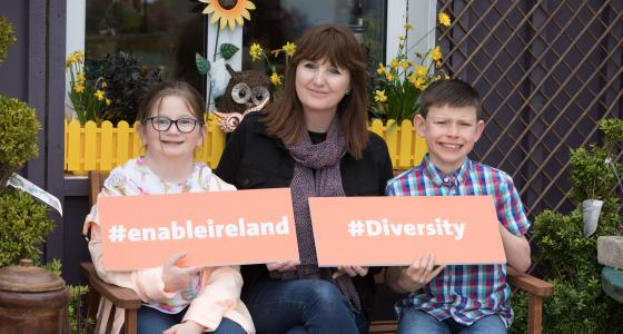 A girl, woman and boy sit on a bench in front of a yellow flower box and hold two signs saying #enableireland and #diversity