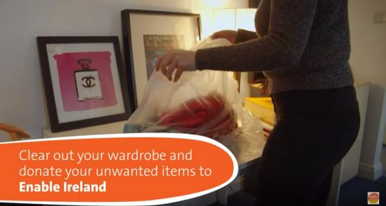 Woman fills a bag of clothes to donate to Enable Ireland