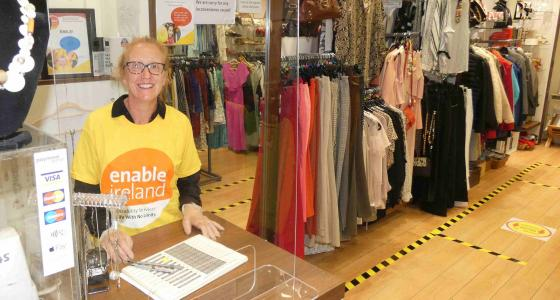 Woman in yellow Enable Ireland t-shirt stands behind a shop counter