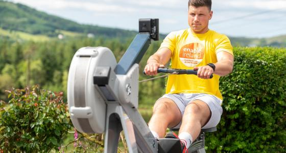 Image shows Munster Rubgy player Fineen Wycherley on a rowing machine training for the Wheel 100 fundraising event
