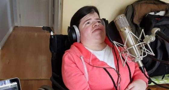 Woman using a wheelchair sings into a microphone