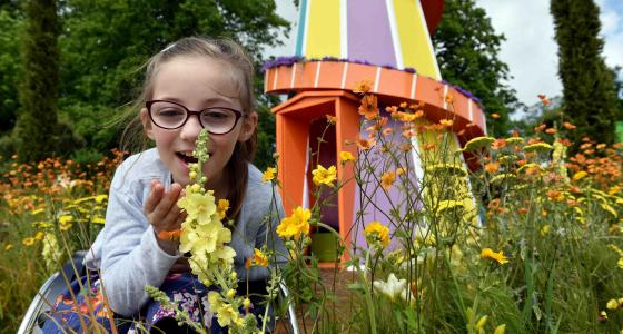 Girl smells yellow flower in front on colourful helter skelter