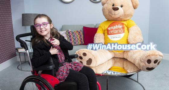 Girl smiling in wheelchair beside giant teddy bear