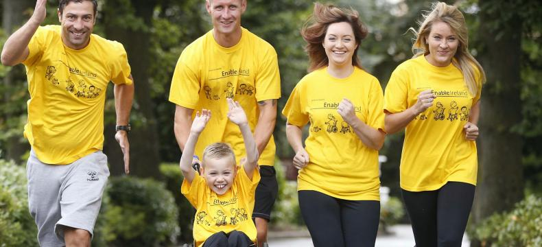 Four runners in yellow Enable Ireland t-shirts pushing a young boy in a wheelchair