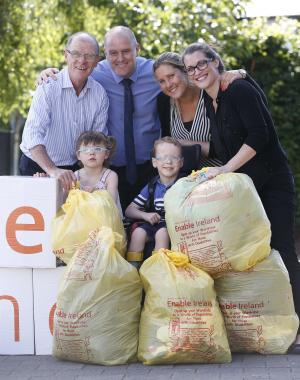 Four individuals in office clothing stand behind two children from Enable Ireland services with four yellow bags of donated items