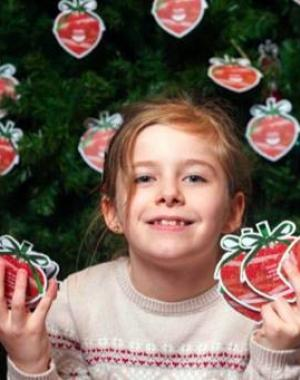 Young girl holds up paper baubles in front of Christmas tree