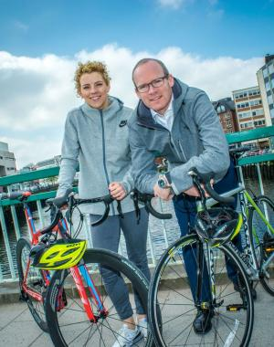 Valerie Mulcahy and Minister Simon Coveney leaning on bikes on a bridge over the river Lee