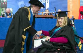 Woman in wheelchair wearing cap and gown receives certificate from college dean in cap and gown