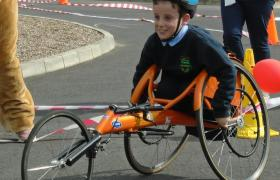 Young boy in orange sports wheelchair competes in race