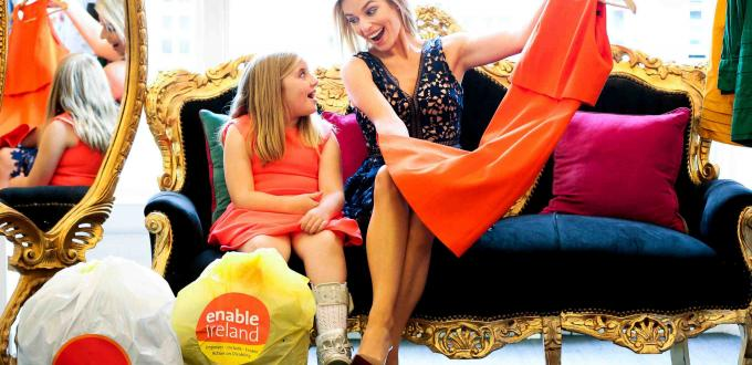 Pippa O'connor and Enable Ireland service user Eva McHugh hold up a red dress while sitting on a blue sofa