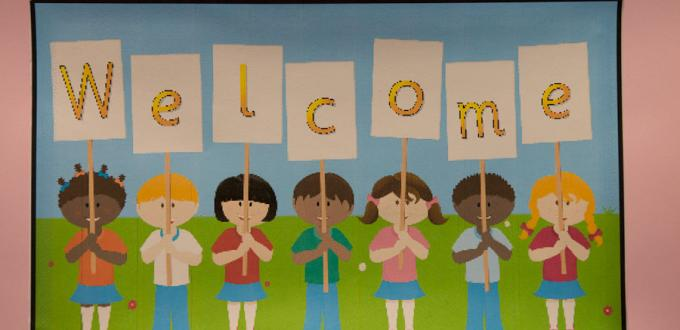 Colourful, hand drawn image of children holding a welcome sign