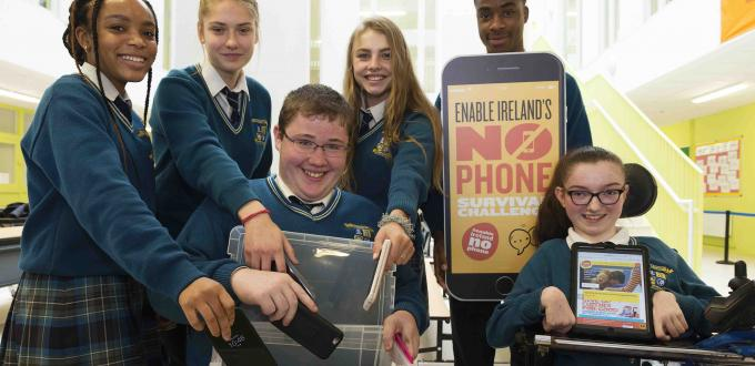 School children in uniforms put mobile phones into clear plastic box and hold up No Phones signs