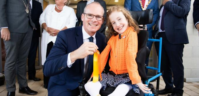 Man in suit beside young girl in wheelchair holding a cut ribbon with people in background
