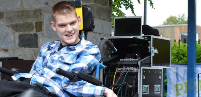 Young man in a wheelchair with music equipment in the background