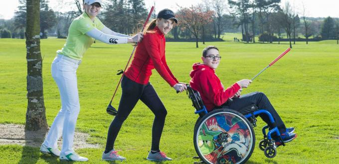 Two female golfers pushing boy in wheelchair with golf club on a golf course