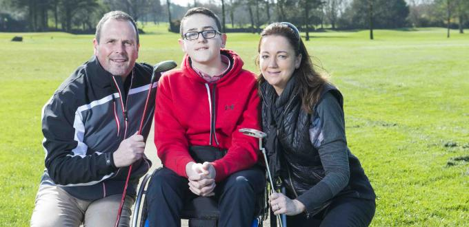 Boy in wheelchair in red top with man and woman on either side holding golf clubs