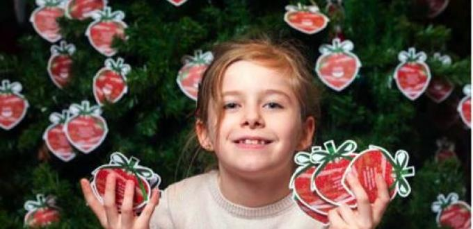 Young girl holds paper baubles in front of Christmas Tree