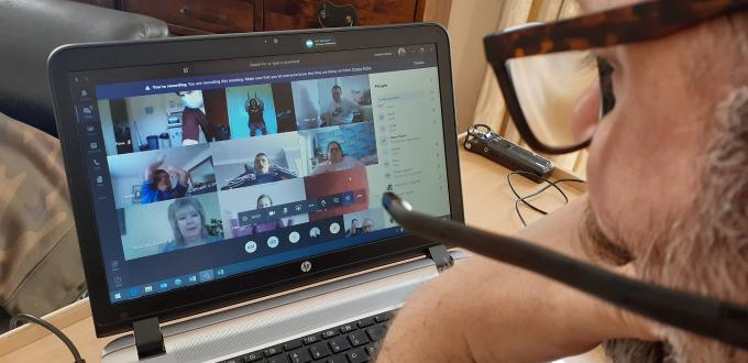 Man wearing glasses looks at a laptop screen showing video conferencing