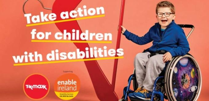 Boy in wheelchair holds giant red hanger with TK Maxx and Enable Ireland logos