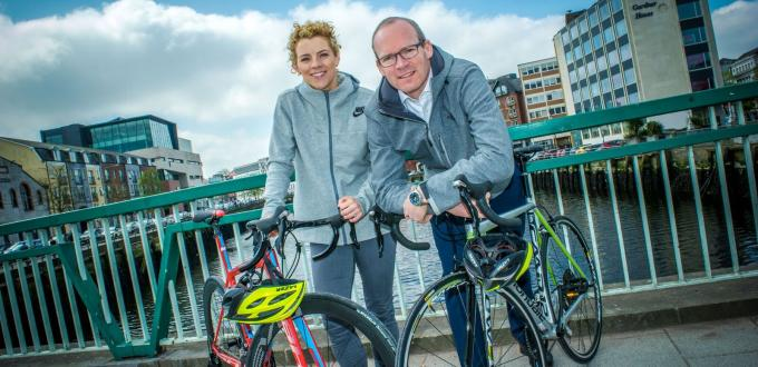 Valerie Mulcahy and Minister Simon Coveney lean on bikes on a bridge over the river Lee