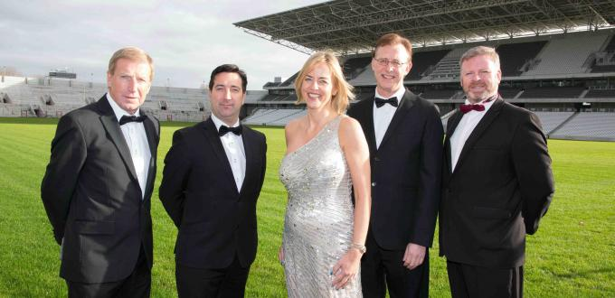 four men in tuxidos and one woman in a grey evening dress line up in from of football pitch