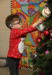 young boy in christmas jumper hands baubles on tree