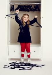 Girl holds up two black hangers in front of white wardrobe
