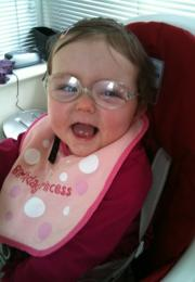 Young girl wearing glasses with pink princess bib and big smile
