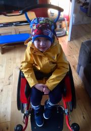 Boy in orange jacket in a wheelchair smiling