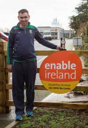 Man stands next to garden gate with Enable Ireland logo and tidy towns award
