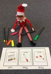 Elf sits on the ground with markers and paper in front of him