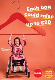 Girl in wheelchair holding up giant red hanger with TK Maxx and Enable Ireland logos