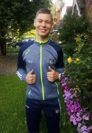 Young man smiles in garden with thumbs up