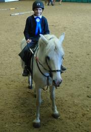 Young boy sits on a white horse