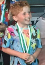 Smiling boy in colourful shirt holds medal