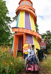 Colourful helter skelter with girl in wheelchair, boy and adult in wheelchaire in the foreground