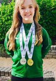 Girl wearing green with medals around her neck