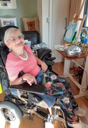 Elderly lady in a wheelchair seated in front of painting workspace