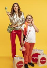 Girl in white t-shirt and yellow seventies headscarf and woman in silver jacket both holding retro phones stand against yellow background with shopping bags with TK Maxx logos on the ground
