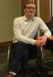 young man in wheelchair smiling at camera