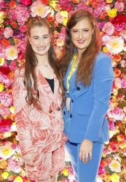 Two young women stand side by side against a floral background