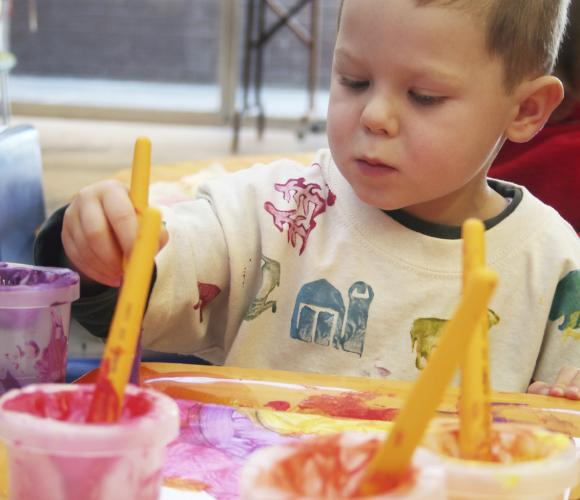 Young boy holding a paint brush in brightly coloured bib